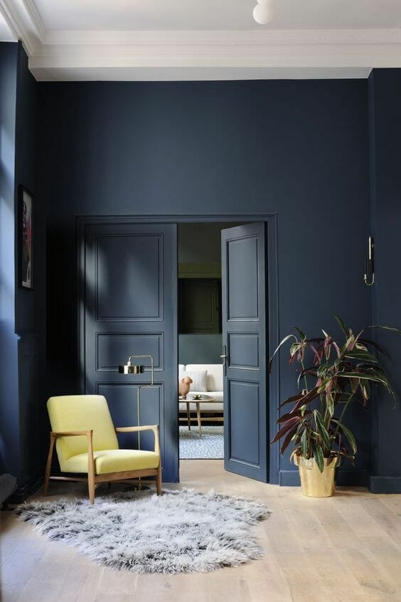 Navy blue walls and doors with modern yellow armchair.