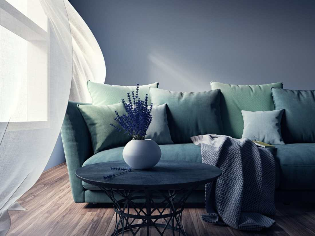 A blue-green couch with many pillows and white curtains flowing in the wind. Tar Heel Painters Chapel Hill, NC