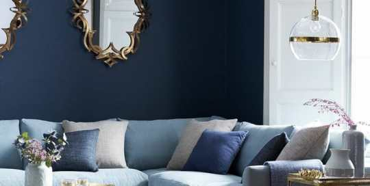Ornate mirrors hang on a navy blue wall. A light blue sectional couch with gold-colored side tables.