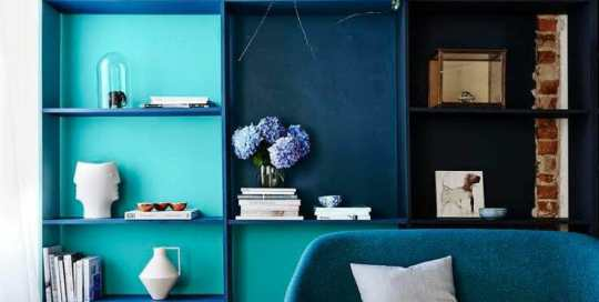 A modern blue armchair in front of custom blue shelving unit.