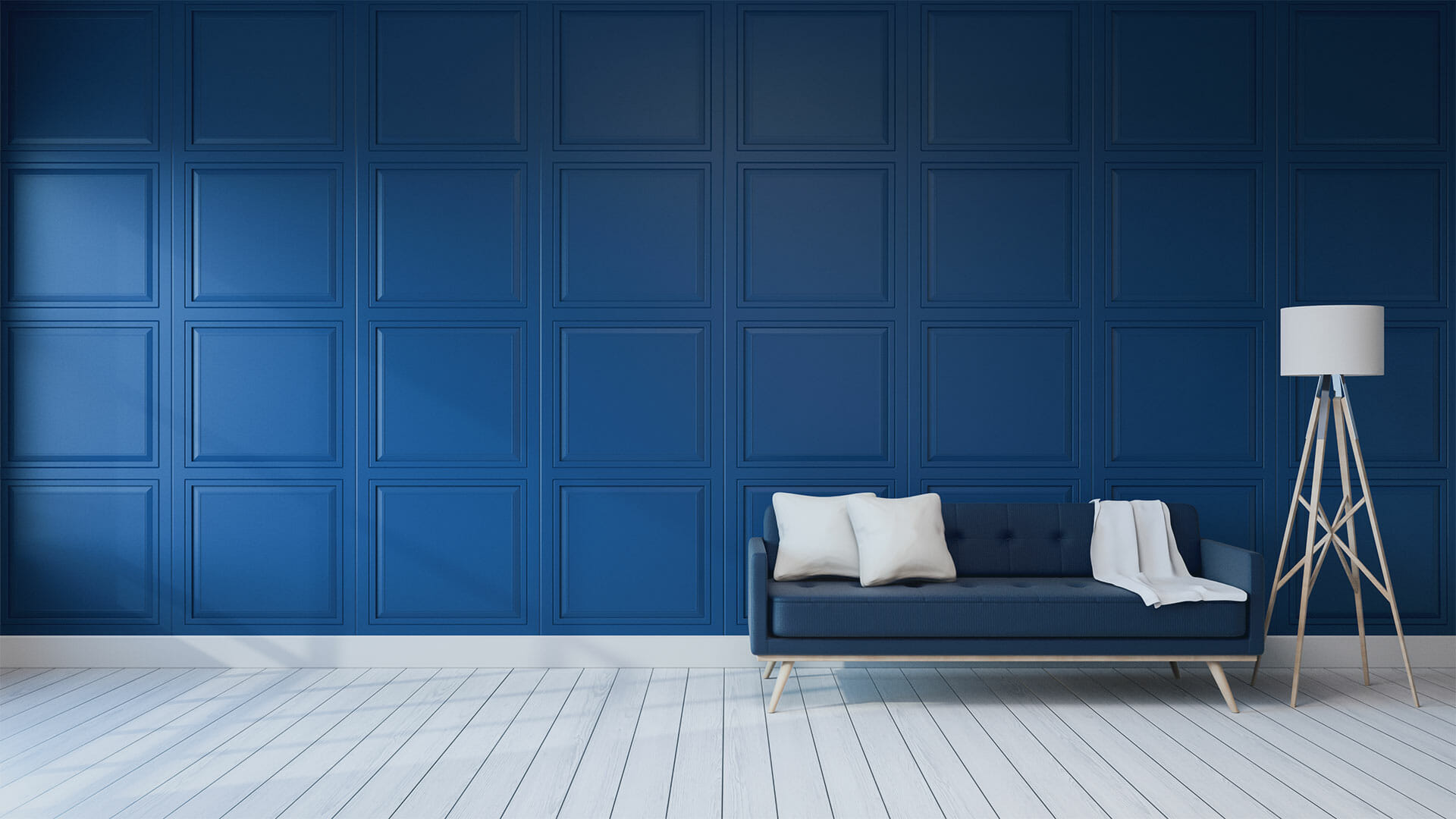A blue paneled wall with a blue 50s style couch and lamp.