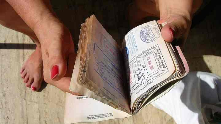 person showing visa section of passport, which they are accused of obtaining via visa fraud