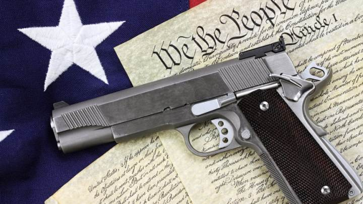 Handgun lying over a copy of the United States constitution and the American flag.