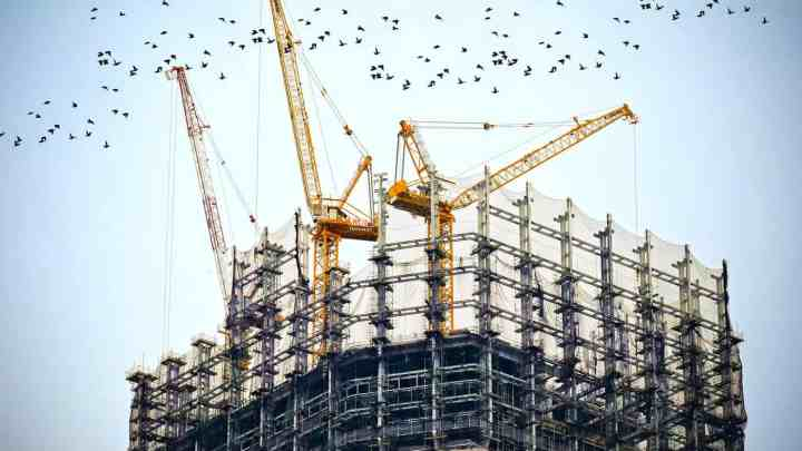 a construction site with large cranes hanging over the building