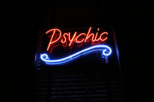 Tarot Reading Reviews red neon sign in window that says psychic with a blue curly line underneath