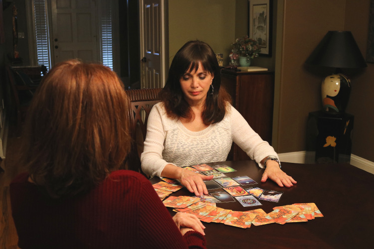 dining room table with a large tarot spread and two women looking over the cards