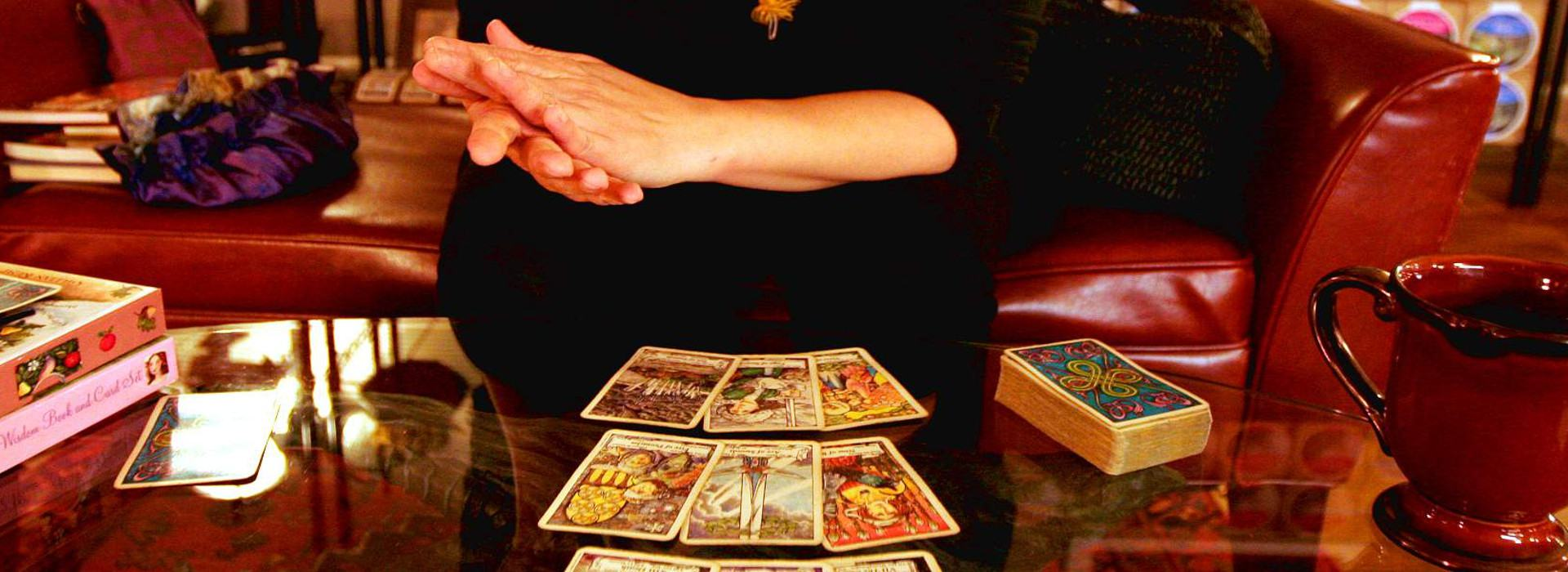 soft female hands pressed together over a tarot card reading layout