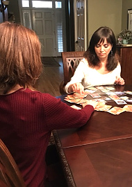 adrianne seated at a wooden table with a client who is asking about a card