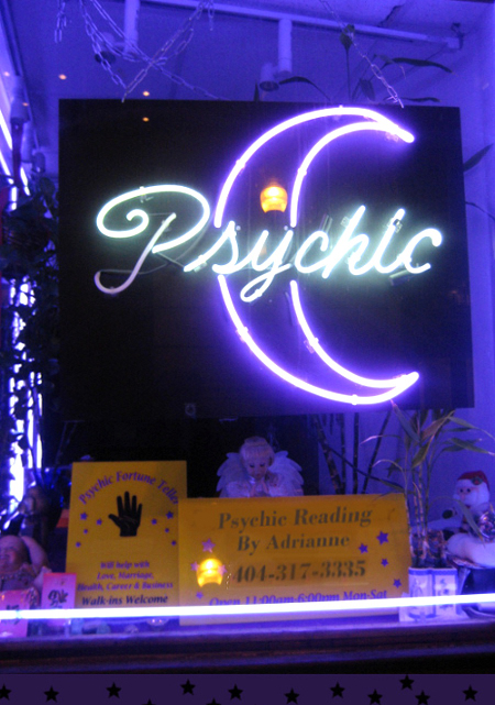 neon sign that says psychic with a moon outline in a small shop window bright shades of blue