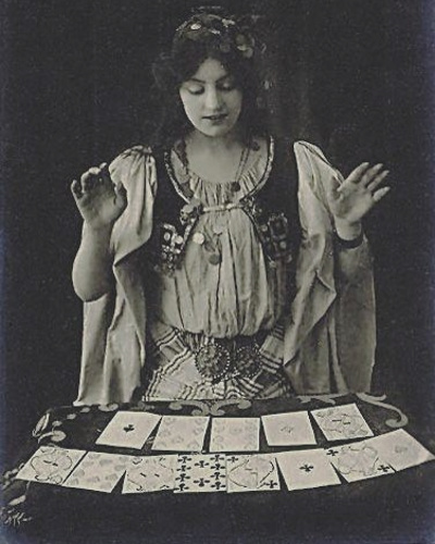 old pic of a gypsy standing and looking down on tarot cards
