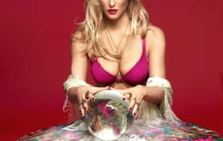 An image of an well endowed woman with long blonde hair she is sitting at a table with tarot cards fanned out the background is a fiery red she is wearing a red bikini top and she is very, very beautiful.