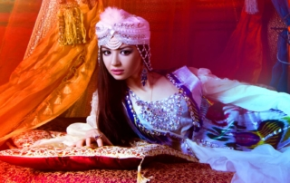 An image of a fortune teller or tarot card psychic laying on pillows she has dark brown hair a pink turgin on and sexy gypsy like clothing she is looking at the camera but not smiling, she also has very plump red lips.