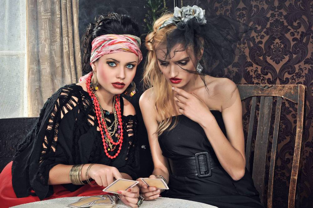 An image of 2 women sitting at a table with tarot cards spread out on is dressed like a fortune teller circa 1920 and the other woman is dressed like a flapper, they are both extremely attractive