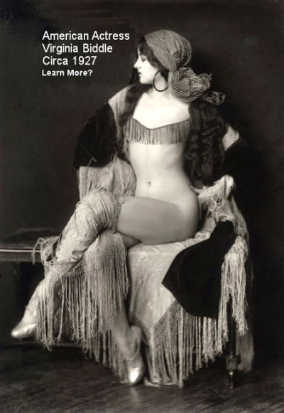 A black and white image of Virginia Biddle (1910 – 2003) scantily clad with what looks like Tarot Card - Psychic garb. She is seated on a couch and facing left in the frame. She has big hoop ear rings on, a head scarf and a shawl. Her legs are crossed, and she has a tassel garb across her chest. Most of her body is uncovered. She has very long dark hair and she is a very attractive woman.