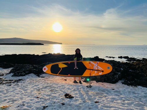 Girl with paddle board at coral beach