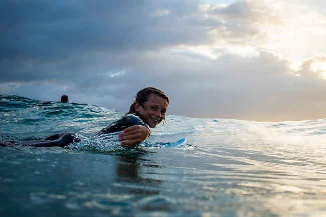 Niño remando en el mar