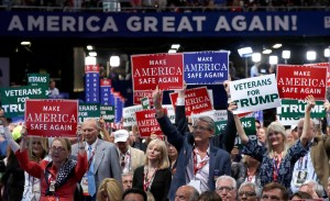 Delegates hold up signs and cheer during first day of the Republican National Convention in Cleveland, Monday, July 18, 2016. (AP Photo/Carolyn Kaster)
