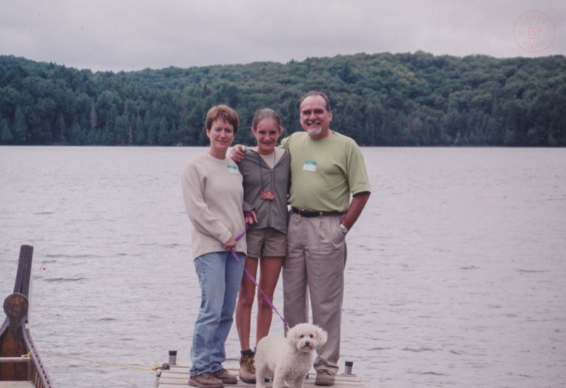 family of three with dog standing on a lakeside dock