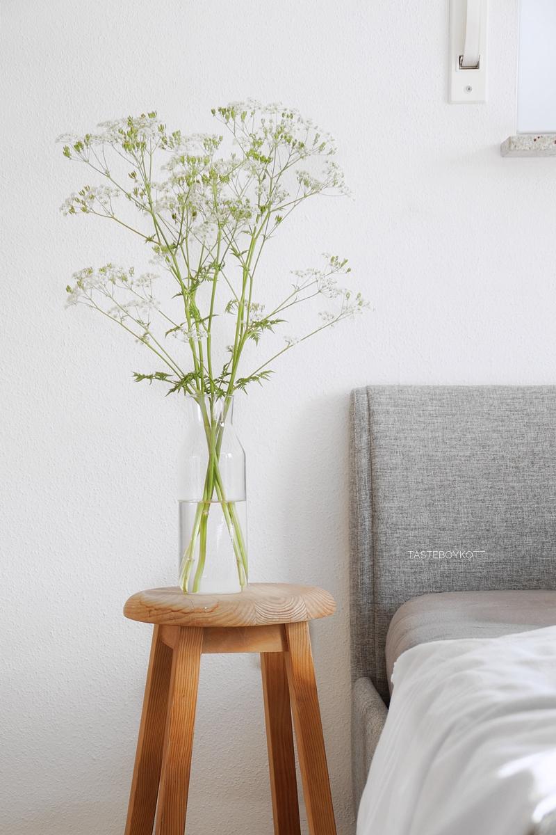 Sommerdeko im Schlafzimmer mit weißen Wiesenblumen in Glasvase, Holzhocker als Nachttisch, graues Bett. Modern skandinavisch schlicht minimalistisch reduziert monochrom dekorieren einrichten wohnen Interieur Interior Design Wohnideen Wohninspiration Tasteboykott Wohnblog