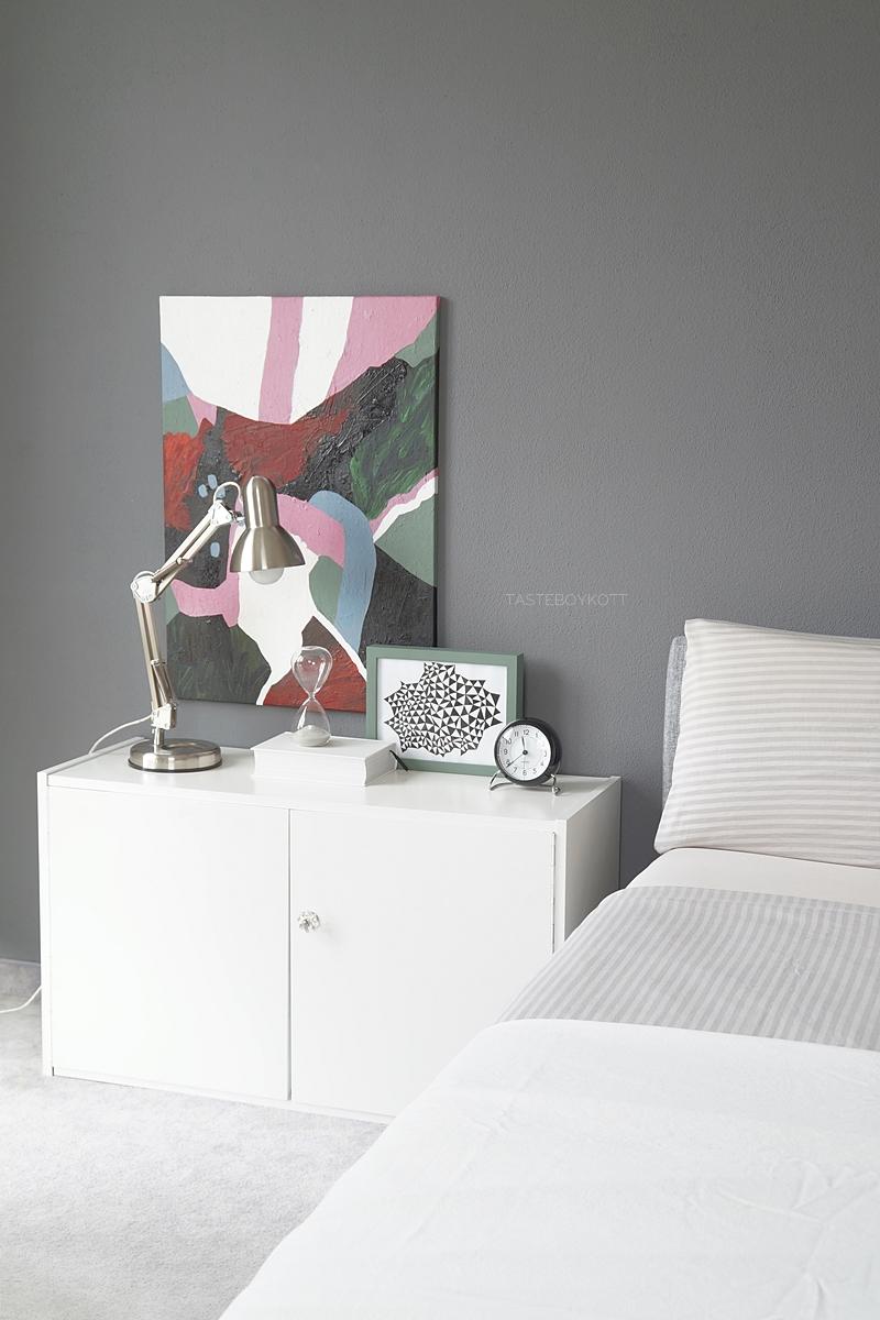 Skandinavisch monochromes Schlafzimmer mit dunkelgrauer Wandfarbe, Polsterbett, abstrakter bunter Kunst als Wanddeko, modernen weißen Kissen und Sideboard als Nachttisch einrichten. Wohnideen Deko Wohninspiration Tasteboykott Wohnblog.