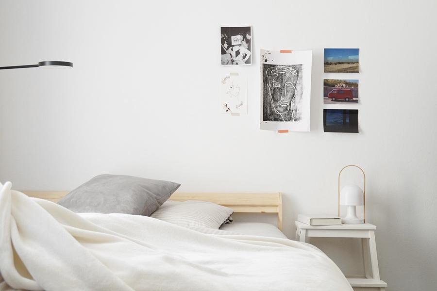 Schlafzimmer in grau-weiß-Holz mit Ikea Bett, Kissen, Stehleuchte und Kunst als Wanddeko