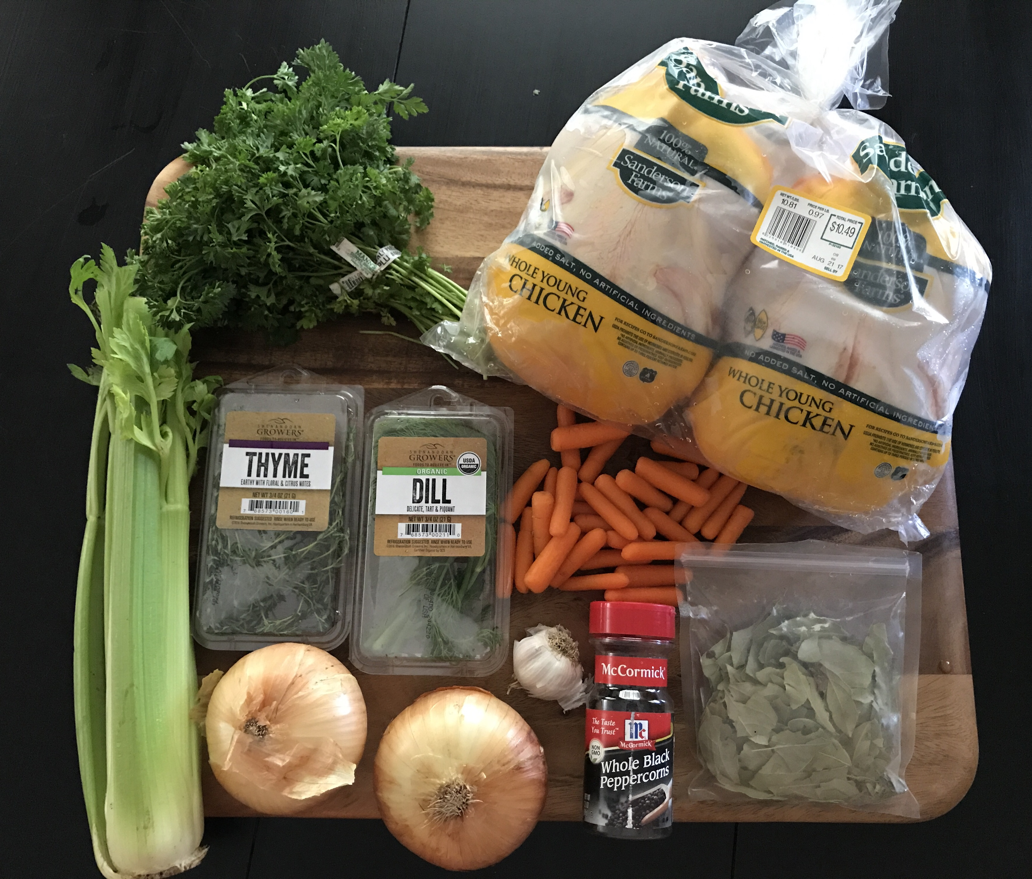 Ingredients for homemade chicken broth on a cutting board: chickens, parsley, onion, garlic, carrots, celery, dill, thyme, bay leaves, peppercorns
