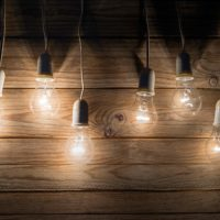 Light bulbs hanging in from of wooden wall to represent answers, frequently asked questions, FAQs, what is life coaching, Questions about life coaching, health coaching