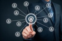 Email marketing newsletter and bulk mail concepts. Businessman click on button with at sign linked with people icons.