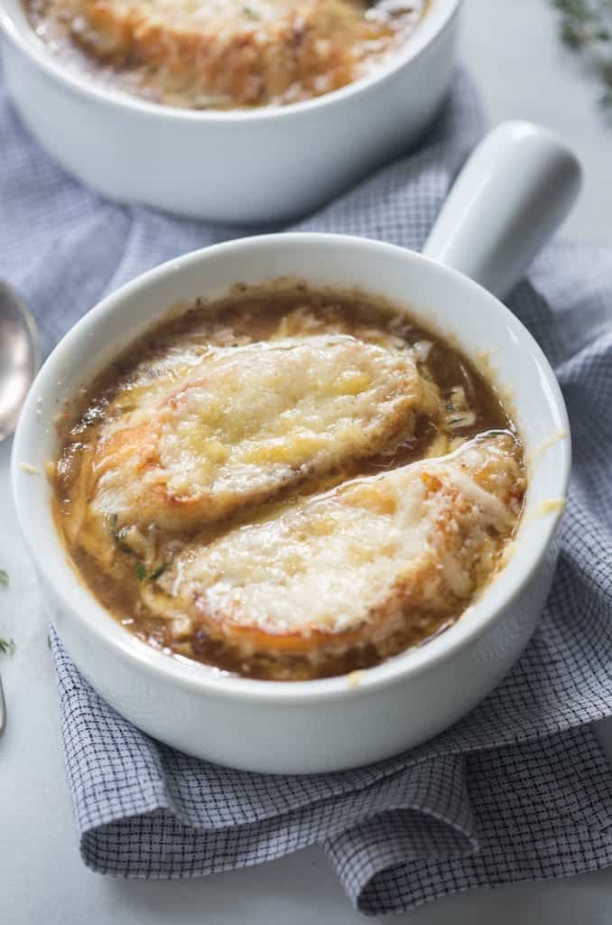 A soup dish filled with homemade French Onion Soup .