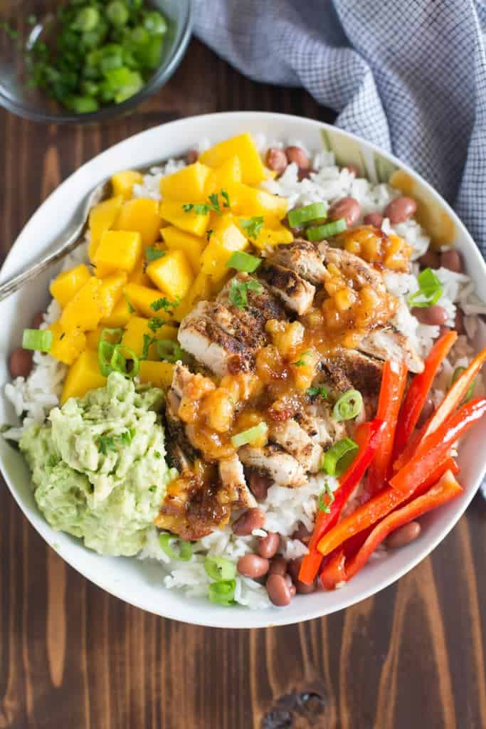 These delicious Caribbean Jerk Chicken Bowls start with a layer of coconut rice and red beans topped with jerk seasoned chicken, mangos, mashed avocado and a sweet and spicy pineapple sauce. | tastesbetterfromscratch.com