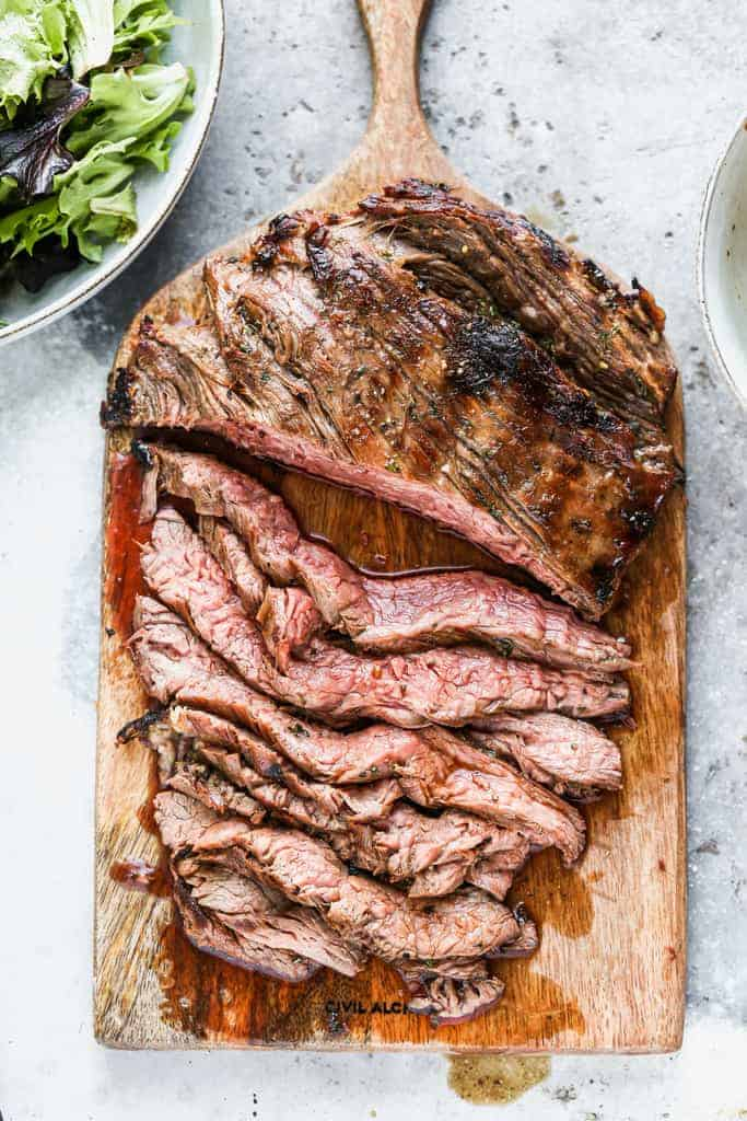 Marinated Flank Steak on a cutting board, with part of the steak cut into thin slices.