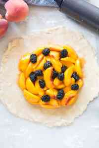 The first step in making a peach blackberry tart! Roll out your pie crust and layer peaches and blackberries in the center   tastesbetterfromscratch.com