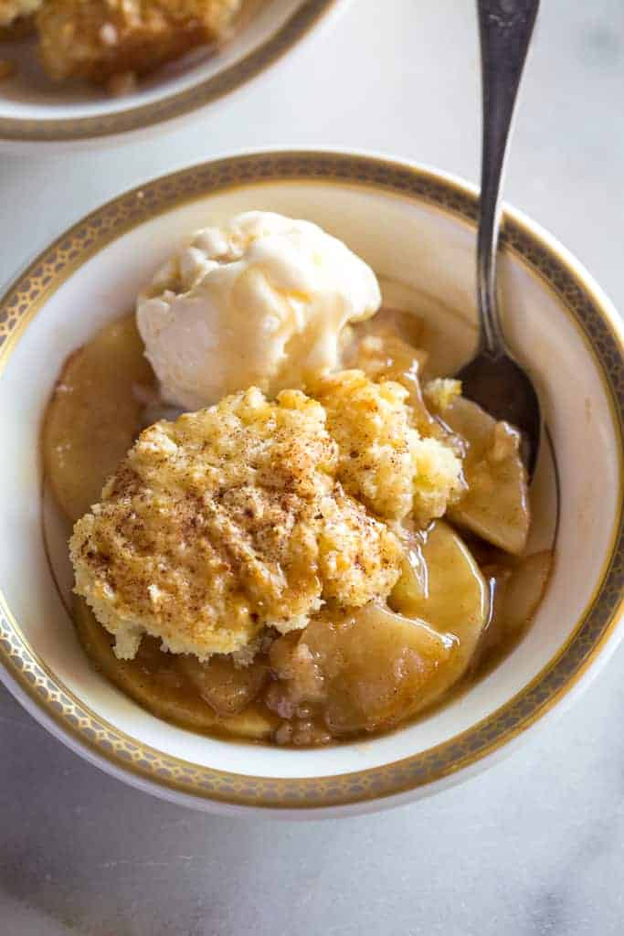 A cream bowl with gold rim full of apple cobbler and a scoop of ice cream.