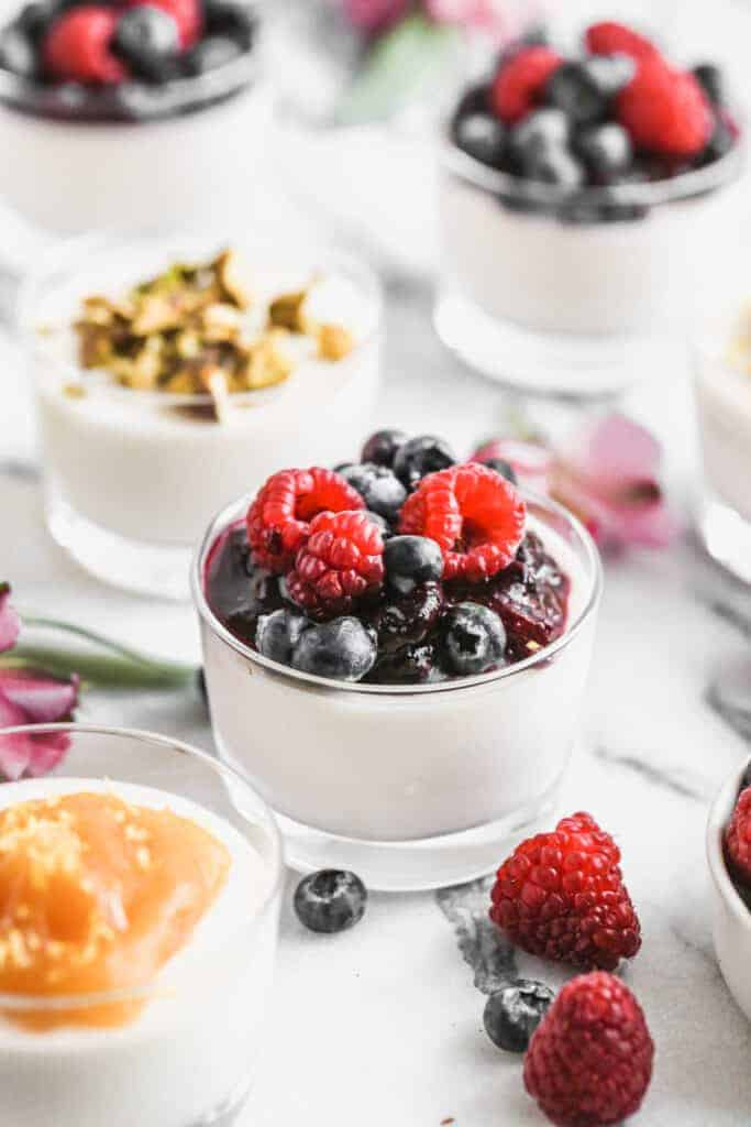 Panna Cotta in a cup with berry sauce and fresh berries on top.