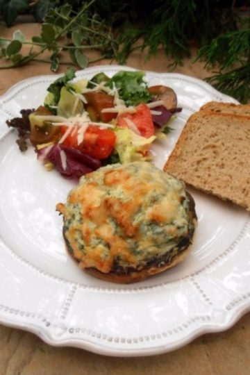 An image of Mushrooms Stuffed with Ricotta and Spinach, a salad with tomatoes and slices of bread on a white plate.