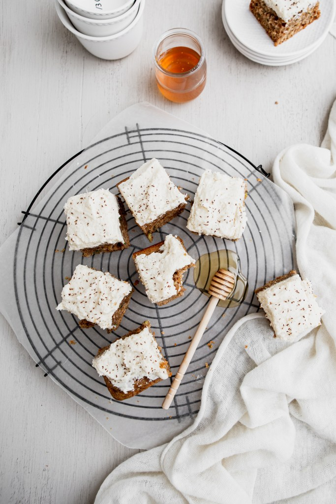 zucchini cake squares with frosting and a honey stick