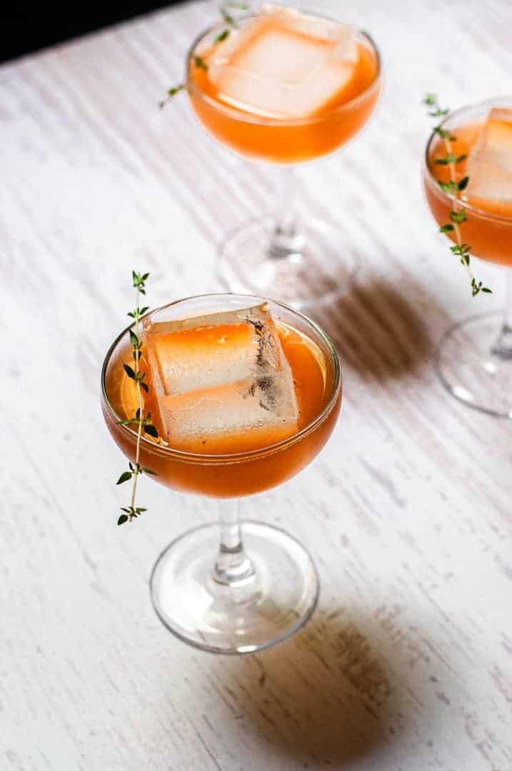 Bourbon and Thyme Peach Smash on a wooden board