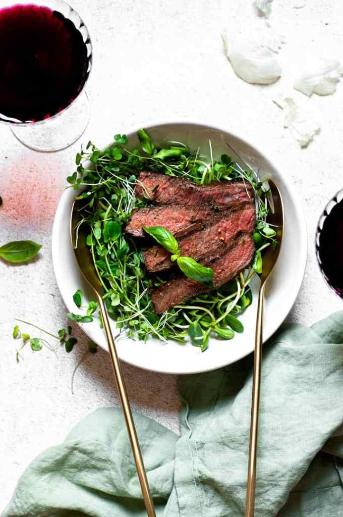Skirt steak on a bed of microgreens with serving spoons and glasses of wine