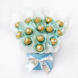 """14 Ferrero Rocher chocolates """"leafed"""" with baby blue cello, all elegantly surrounded in white cello in a small baby blue box."""