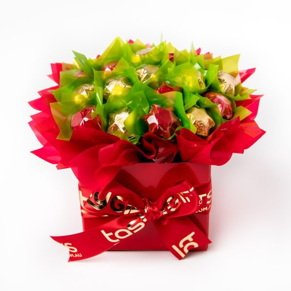 """19 red and gold foil wrapped milk chocolate stars, """"leafed"""" in green, surrounded by red cello in a small red box."""