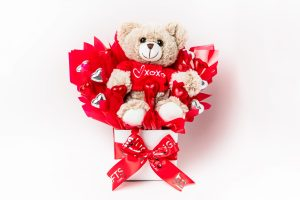 A Coco bear soft toy with 13 red and silver foil wrapped milk chocolate hearts surrounded by red cello in a small white box.