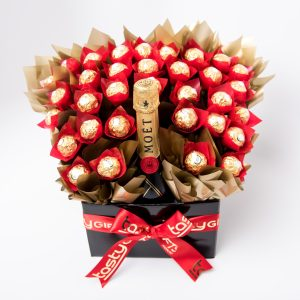 33 Ferrero Rocher chocolates around a 750ml bottle of Moët & Chandon Brut Impérial Champagne NV surrounded by gold cello in a large black box.