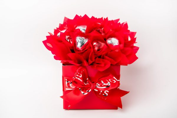 19 red & silver foil wrapped milk chocolate hearts surrounded by red cello in a small red box.