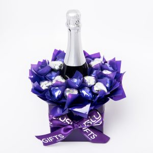A 750ml bottle of Stony Peak sparkling brut NV with 20 purple and silver foil wrapped milk chocolate hearts, surrounded by purple cello in a small purple box.