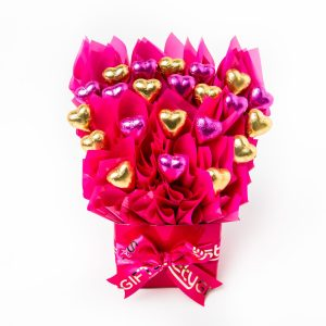 22 pink and gold foil wrapped milk chocolate hearts surrounded by pink cello in a small pink box.