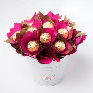 13 Ferrero Rocher chocolates in duo pink/gold cello surrounded by duo pink/gold cello in a small white keepsake metal bucket.