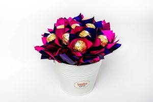 """13 Ferrero Rocher chocolates wrapped in clear cello and """"leafed"""" in duo pink/purple cello surrounded by duo pink/purple cello in a small white keepsake metal bucket."""