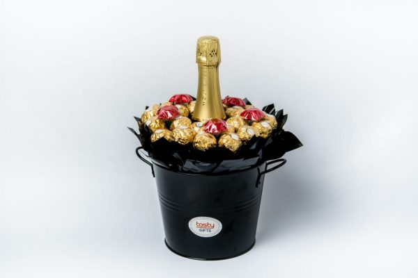 26 Ferrero Rocher chocolates and 5 red foil wrapped milk chocolate stars around a 750ml bottle of Wolf Blass Bilyara sparkling brut surrounded by black cello in a large black keepsake metal bucket.