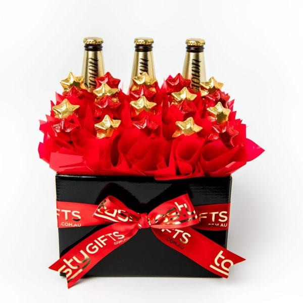 3 Crown Lagers accompanied by 20 red and gold foil wrapped milk chocolate stars, all surrounded by red cello in a large black box.