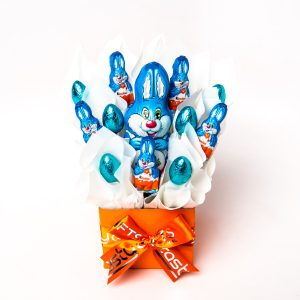 A 75g Kinder Bunny, 5 mini Kinder bunnies and 5 milk chocolate half eggs surrounded by white cello in a small orange box.
